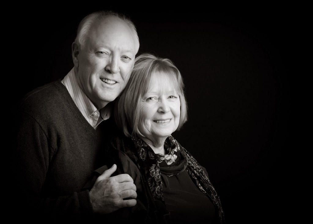 Lovely Elderly couple in monochrome on black background wearhing dark clothes